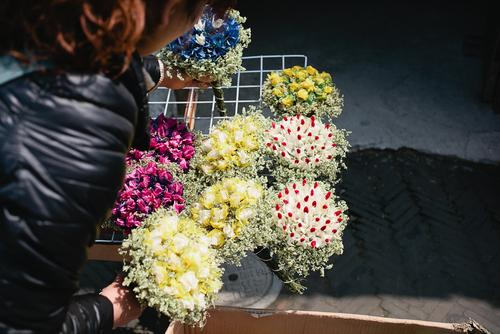 The street vendors sell flowers to couples who stroll the streets.
