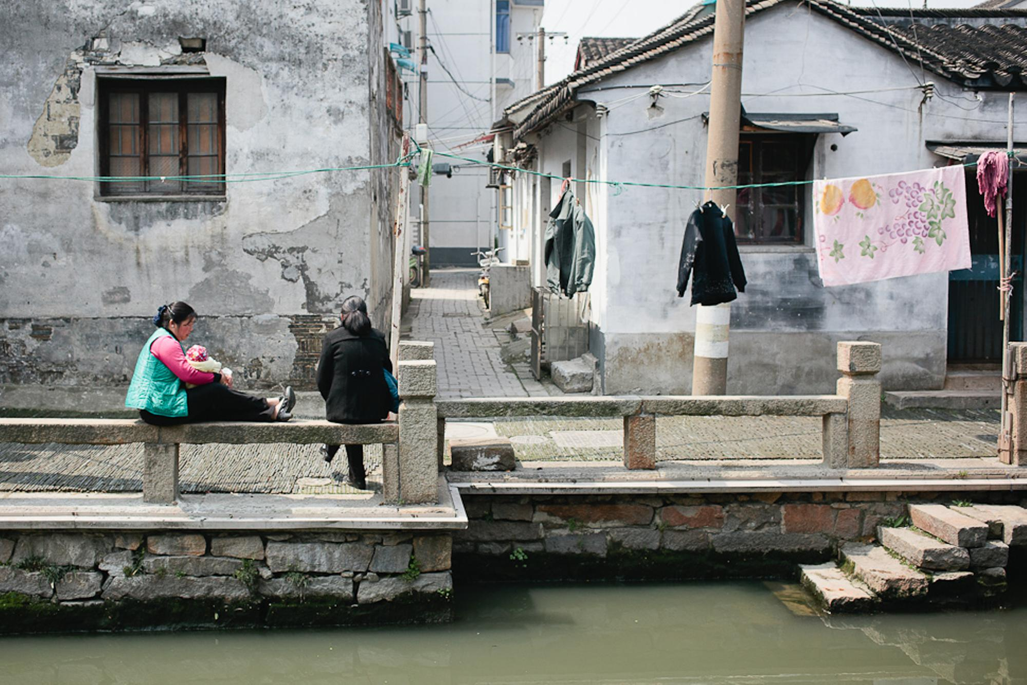 A women nurses a baby and chats alongside the dirty canal water. Why's it so dirty?