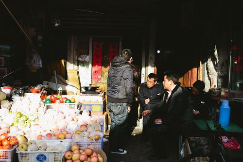 Men chatting as some rare light peeks through the market.