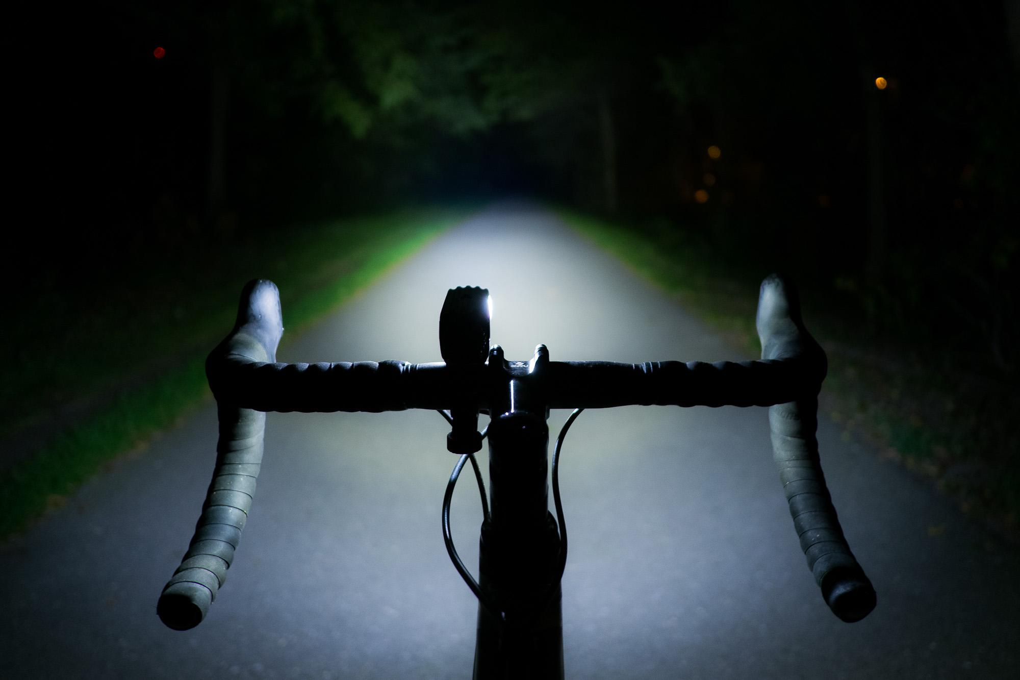 Rider view down a pitch black bike path