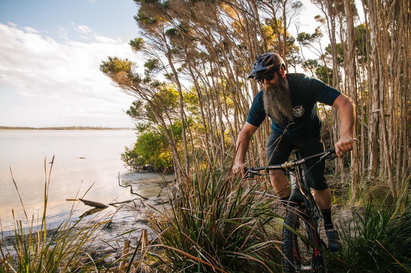 Jimi through the tea trees, with a view of the Tasman sea.