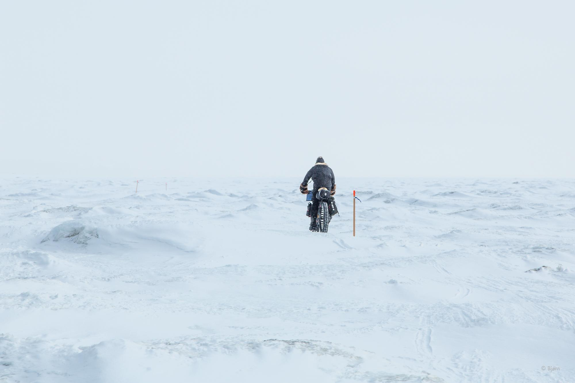 Kim McNett rides over sea ice hummocks on Norton Sound.