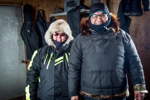 Two travelers take a break from the raging blizzard in a shelter cabin above the Arctic Circle.