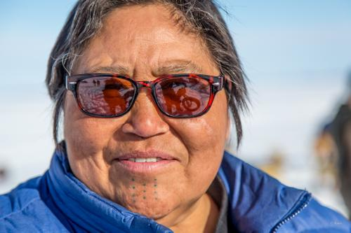A woman with traditional Inupiaq tattoos watches the start of the Kobuk 440 sled dog race.