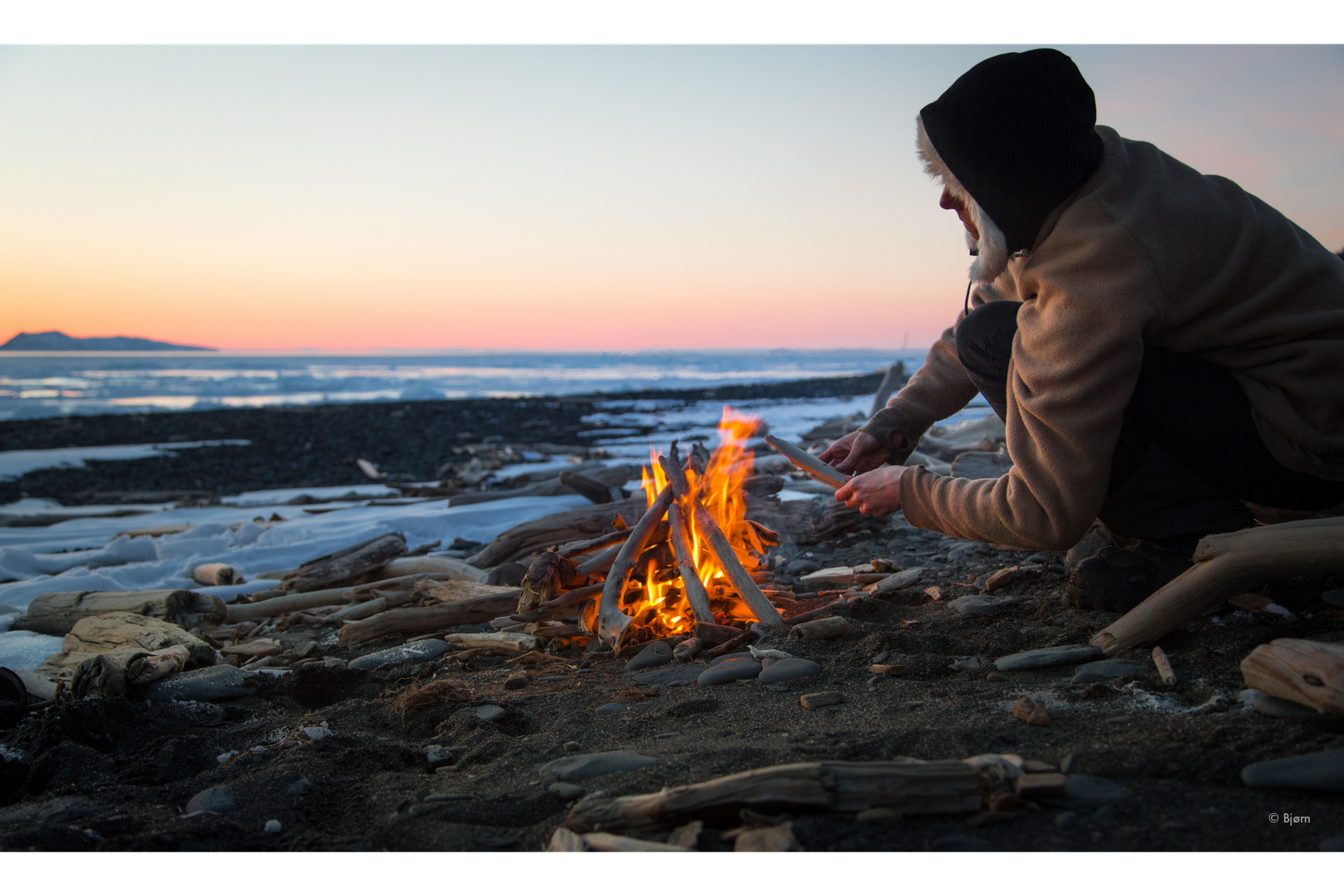 Kim McNett builds a fire to cook dinner on the frozen shore of Norton Sound.