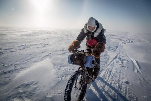 Kim McNett rides over wind drifted snow just below the Arctic Circle.