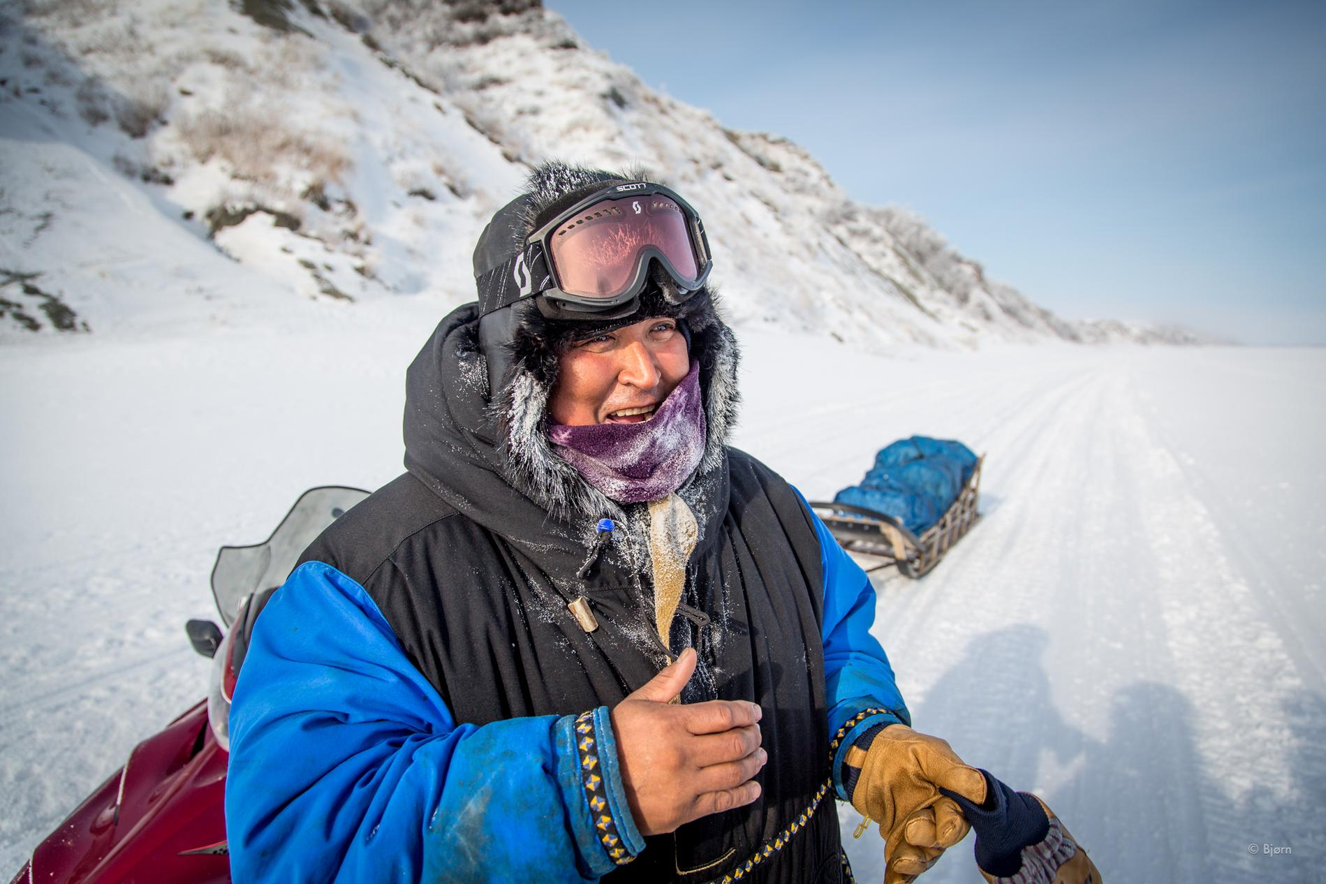 A generous hunter stoops to offer Bjørn and Kim a big chunk of Muktuk—bowhead whale blubber. This hunter provides caribou meat to elders who can no longer hunt for themselves.