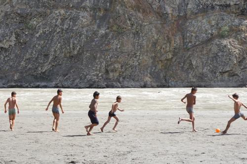 Boys play soccer on the banks of the Panj River, with Afghanistan just beyond.