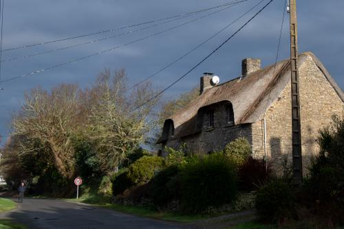 Thatched roofs on stone houses dot the forested countryside of Southwest Brittany.