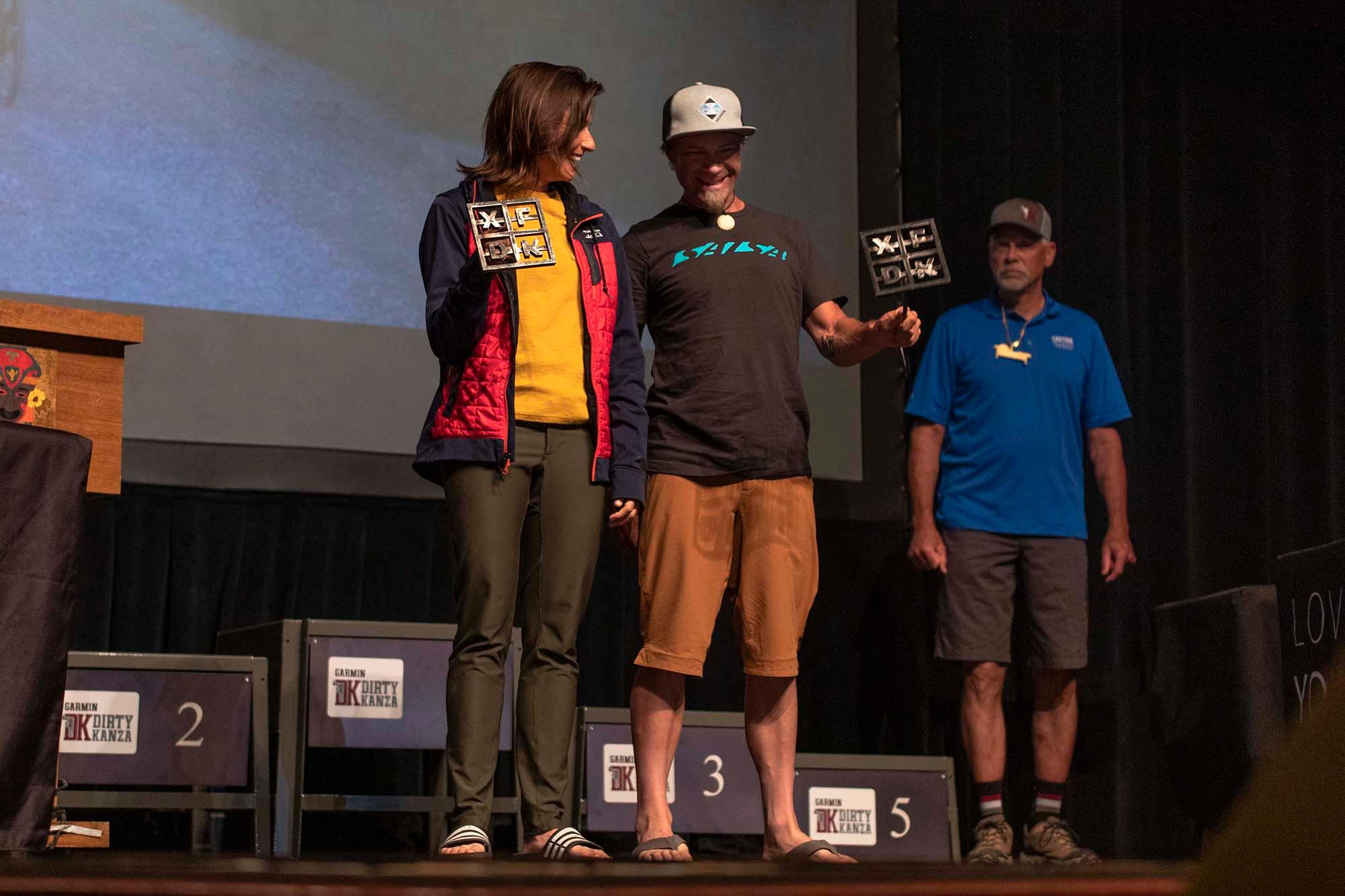 Lael Wilcox, the first female finisher, and Jay Petervary, the first male finisher, accept their DKXL brands. (Rugile Kaladyte)