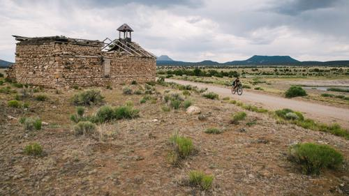 Lael passing a run down barn south of Pie Town, NM (Spencer Harding)