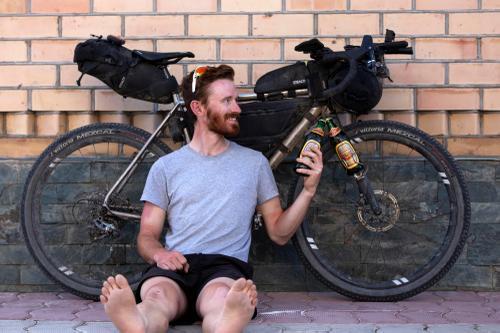 Hayden Stevens cheers his bike in Cholpon-Ata. (Rugile Kaladyte)