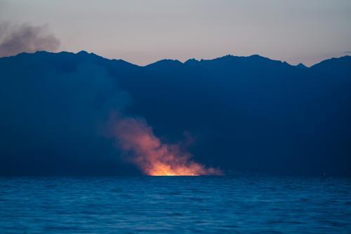 While a big fire blazes across the lake